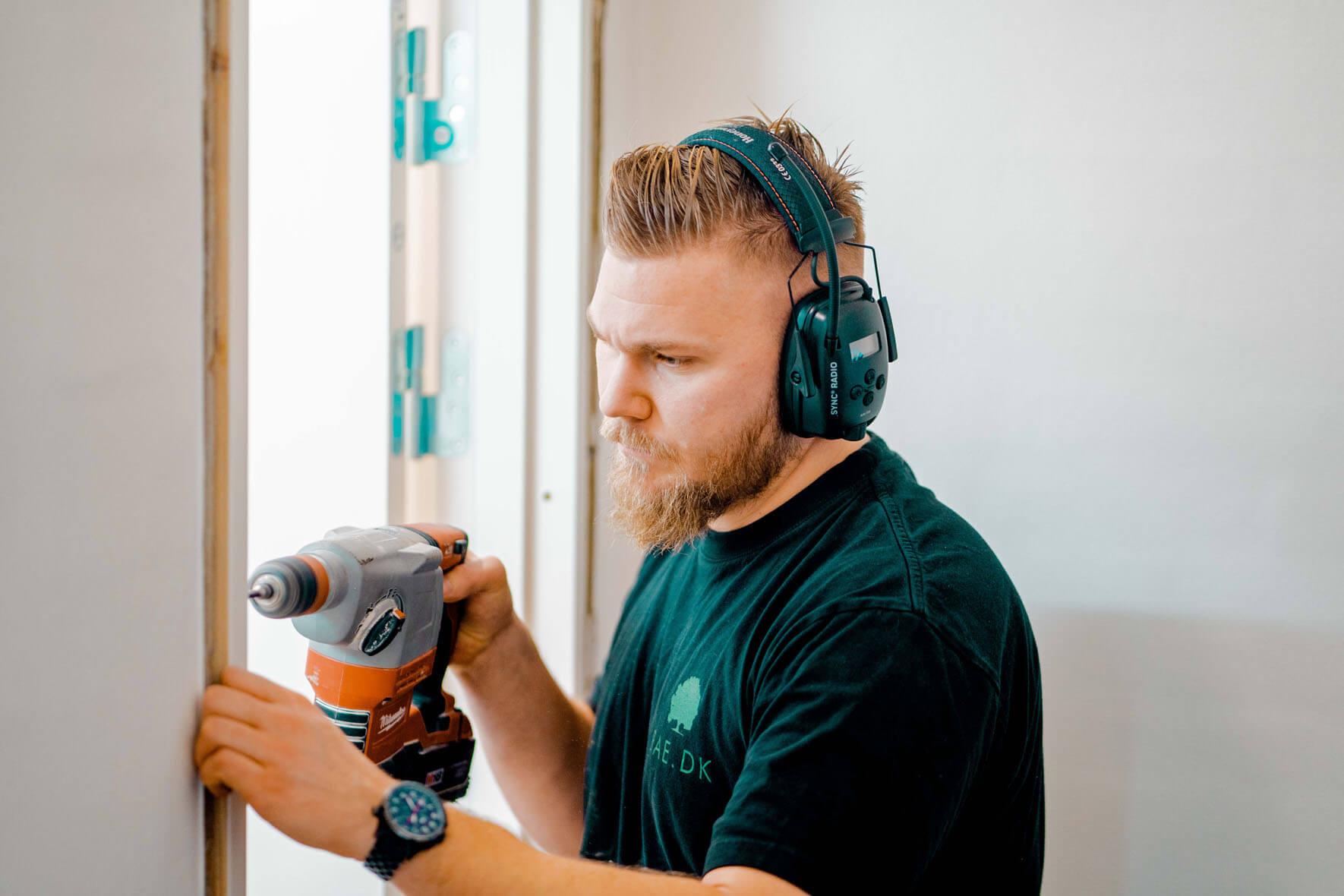 Snedker, tømre, håndværker som monterer dørkarm iført høreværn